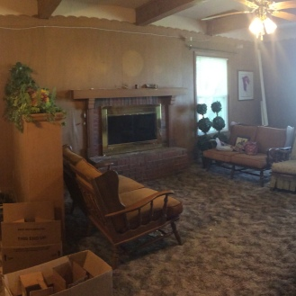 The panoramic of the dining room and living room. The owner is sitting there on the phone.